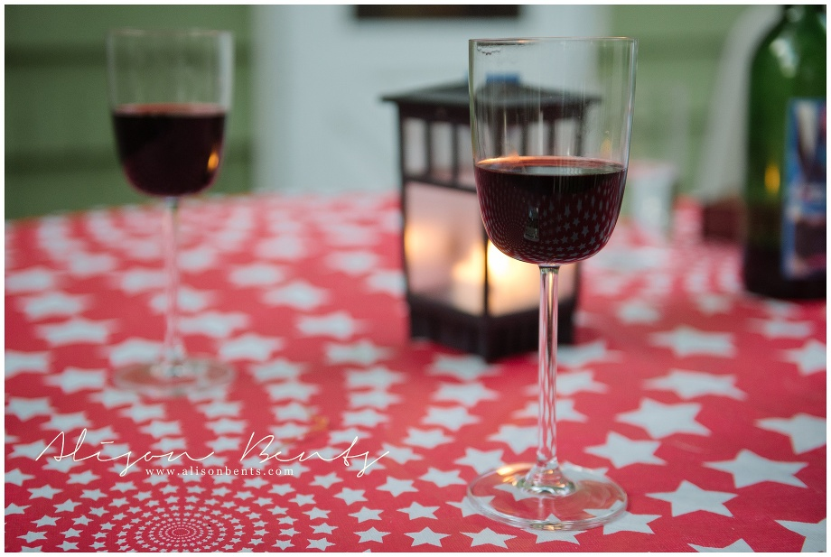 red wine in glasses on picnic table with lantern