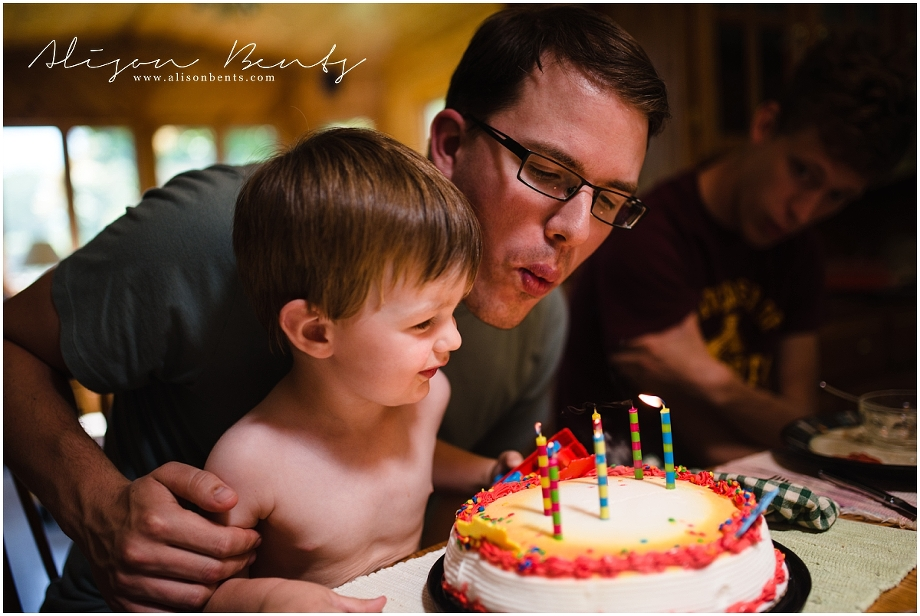 father and son blow out birthday candles on cake